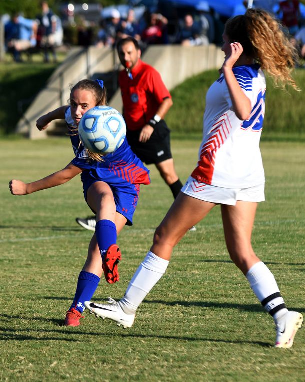 Heritage Academy's Caroline Peal, left, kicks the ball past Starkville Academy's Anna Card, right, during a game Tuesday night at the Columbus Soccer Complex. The game resulted in Starkville's second victory over Heritage this season.