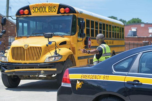 School Resource Officer Sammy Shumaker directs buses out of Armstrong Middle School. Buses transported children to Starkville High School's football field after a gas leak Tuesday afternoon.