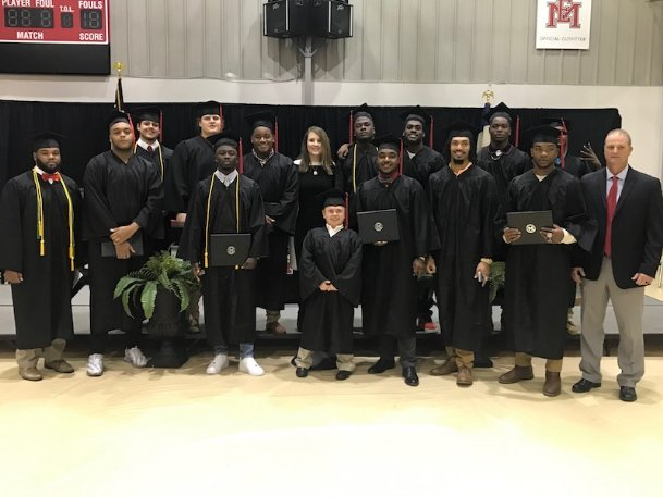 EMCC Athletic Academic Advisor Abby Jenkins poses with the Lions' December graduates, all from the football team. This spring, though, Jenkins didn't get to send off the departing student-athletes, as EMCC held a virtual graduation Wednesday due to the coronavirus pandemic.