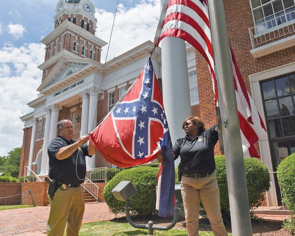 Lowndes County Sheriff Eddie Hawkins unclips the state flag - which displays the Confederate battle emblem in its top left corner - while Lt. Rhonda Sanders holds it on Monday afternoon at the Lowndes County Courthouse. The Senate voted 37-14 to retire the flag and the House voted 91-23 on Sunday.