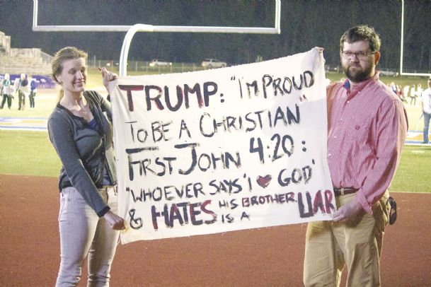 Erin and David White display a banner protesting Donald Trump at the Madison Central High School football field. The Trump campaign said an overflow crowd of 7,000 people watched the rally Monday at the school's football stadium.