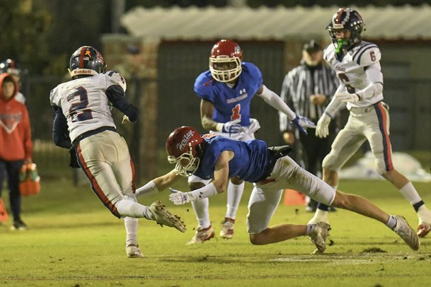 Heritage safety Noel Fisher (5) wraps up a Leake Academy ball carrier in Friday night's game.