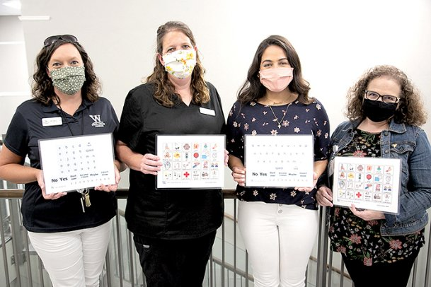 Mississippi University for Women faculty members, from left, Ashley Alexander, Stephanie Kelley, Janette Hreish and Laura Bell hold communication boards created for health care providers and families to communicate with patients on ventilators or too weak to speak.