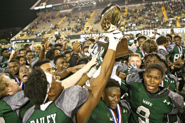 Members of the West Point High School football team hold up the Mississippi High School Activities Association (MHSAA) Class 5A State Championship trophy Saturday night after beating West Jones 27-12 to win the program's third-straight title.