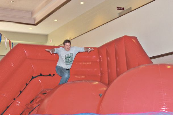 """Gerald """"Boo� Matthews Jr. leaps in an attempt to make it across the """"Big Baller� bouncy house at a youth group Super Bowl watch party Sunday in the Starkville First United Methodist Church gymnasium. Matthews is a plant scientist who volunteers with various church functions and even holds a second job as a Starkville-MSU Area Rapid Transit driver."""