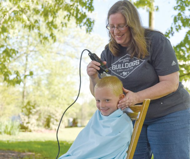 Six-year-old Toby Carpenter sits still as his mom, Dawn Carpenter, cuts his hair with clippers on a warm early April afternoon outside their house in west Lowndes County. Cutting hair at home is routine for the Carpenter family, which includes eight children. For many, though, a month without barbers and stylists during current COVID-19 closures, begs the question: