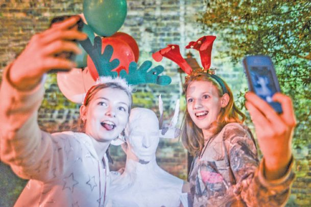 "Lily Dunn, 12, left, and Abbie Barton, 13, take ""selfies� with a piece of installation art at Leadership Plaza during Wassail Fest Friday. Lily is the daughter of Jenny LeBlanc, of New Hope, and Aaron Dunn, of Tupelo, and Abbie is the daughter of Sarah Reedwood and Charles Barton, of Columbus."