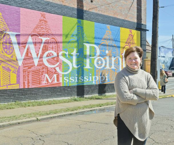 Deborah Mansfield of Deborah Mansfield Decorative Painting poses in front of one of the many murals situated in downtown West Point on Friday. Mansfield has painted four murals throughout the town and is working on a fifth. She produces  these city murals at no charge.