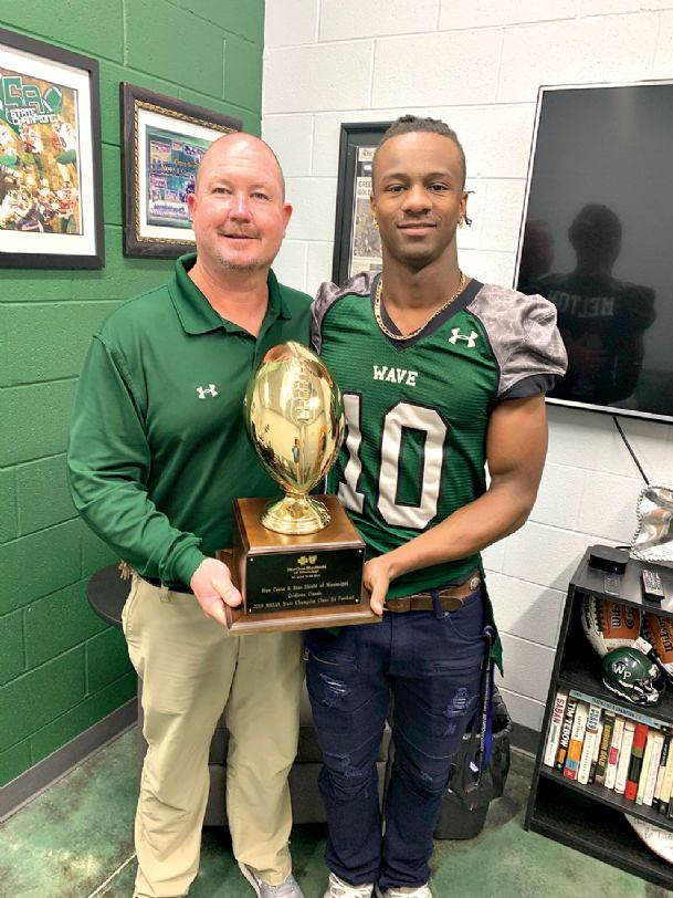 West Point High School football coach Chris Chambless and senior Ryan Melton hold the Mississippi High School Activities Association (MHSAA) Class 5A State championship trophy the team received after beating West Jones 27-12 on Dec. 1 in Hattiesburg. The title was third-straight for the Green Wave.