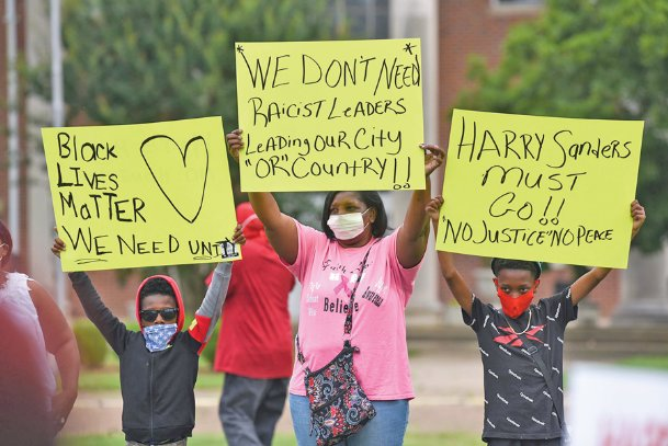 From left, Malachi Turner, 8, Mary Shinn and Demarius Shinn, 10, hold signs during a protest demanding District 1 Supervisor Harry Sanders' resignation on Tuesday outside the Lowndes County Courthouse. The crowd began at the front of the courthouse and then walked to the back entrance that the county supervisors use.