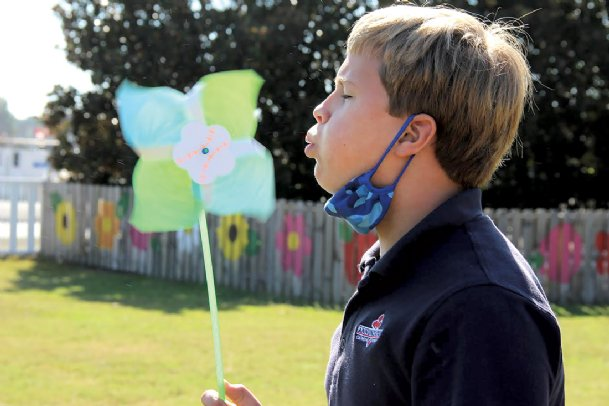Annunciation Catholic School student Campbell Callaway, 11, tests out the pinwheel Thursday he made for his school's participation in a worldwide Pinwheels for Peace project. More than 200 handmade pinwheels will be