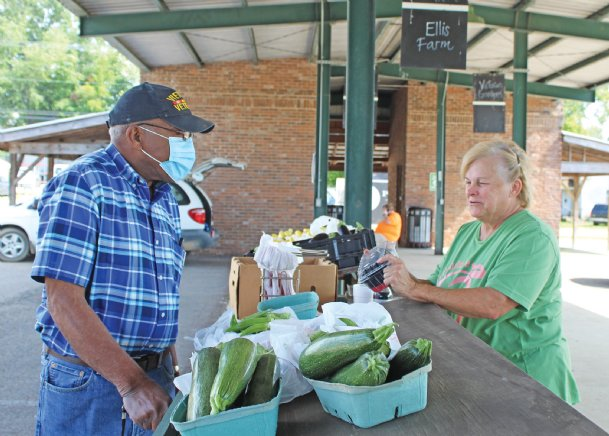 Esther Earnest shows fresh blackberries to Jesse Harris of Columbus at the Hitching Lot Farmers Market Monday in Columbus. Earnest enjoys cooking with the vegetables and fruits grown at her family's Prospect Produce Farm in Houston and shares some favorite recipes today.