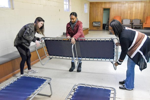 From left, Mississippi University for Women Honor College students Treasure Heath and Cayla Skinner assist Community Outreach Director Glenda Buckhalter Richardson in setting up cots Thursday at the temporary emergency warming shelter in Columbus. The shelter, located at the Farmers Market Annex at the corner of Second Avenue and Third Street North, is open from 5 p.m. to 8 a.m. tonight, Monday and Tuesday nights during sub-freezing temperatures, available for the homeless or for homeowners and renters without heat. Heath is from Starkville. Skinner's hometown is New Orleans.
