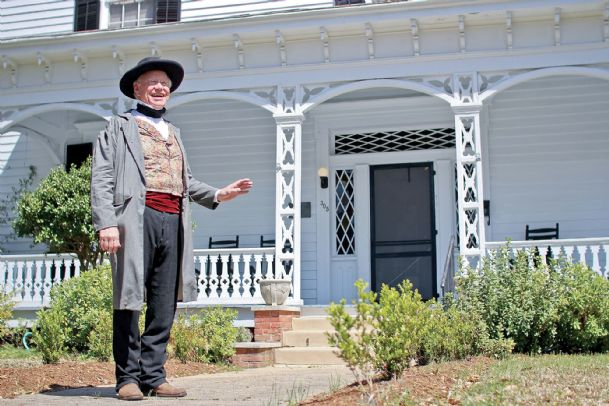 Sid Caradine stands in front of his family's ancestral home, The Amzi Love Home, on Seventh Street in Columbus.