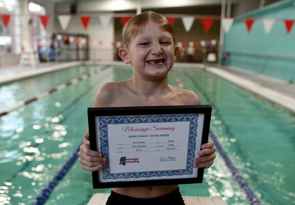 Axel Phillips was awarded a certificate for breaking another state record during swim practice Wednesday afternoon at the Frank P. Phillips Memorial YMCA. Coach Stephanie Gonzalez presented the certificate.