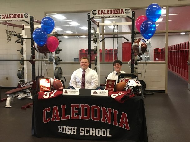 Caledonia High School football players Hayden Barker, left, and Brandon Edmondson celebrate signing their letters of intent to play football at Southwest Mississippi Community College. After a recruiting process heavily impacted by the COVID-19 pandemic, the pair finally held their ceremony Wednesday in the team's field house.