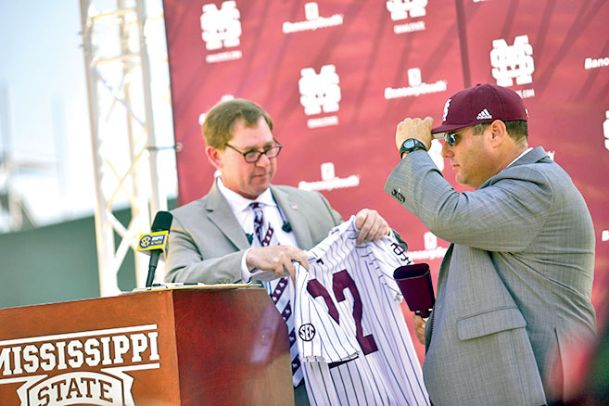 Mississippi State Director of Athletics John Cohen, left, presents new MSU baseball coach Chris Lemonis with his jersey at Lemonis' introductory news conference June 26 at Dudy Noble Field in Starkville.