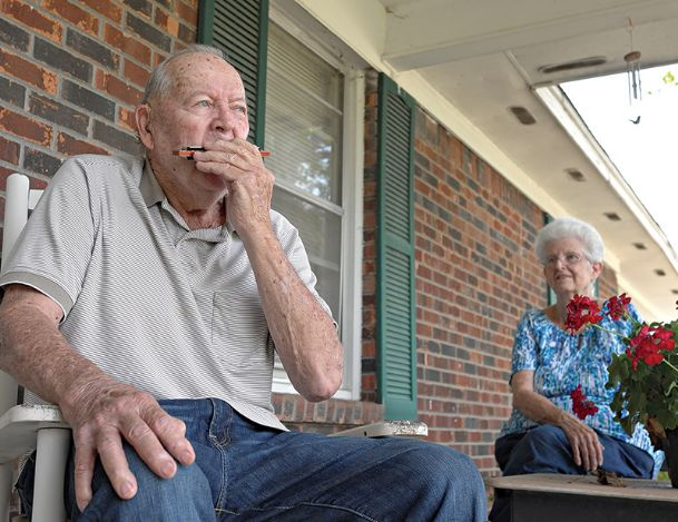 """Bob Fussell plays """"Amazing Grace� with his harmonica on his front porch Saturday morning while his wife, Ann, looks on. The 86-year-old Fussell often gives impromptu performances with the instrument in Kroger and the West Point Walmart while shopping with his wife."""