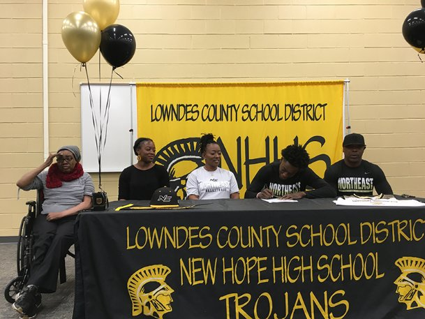 New Hope senior RL Mattix signs his letter of intent to play basketball at Northeast Mississippi Community College on Friday. His parents, sister and grandmother joined him at the table set up in the New Hope multipurpose room.