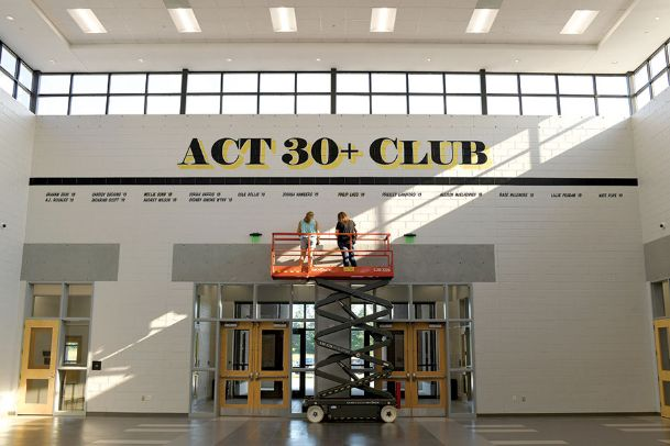 Corinne Beauregard, left, and Jeannie King, both of Columbus, stand atop a scissor lift at New Hope High School Wednesday to work on signage for the ACT 30+ Club. At the request of New Hope High Principal Matt Smith, Beauregard, with King, created the wall by painting 3-foot tall letters and adding names of students who scored 30 or better on the ACT in vinyl letters. With advancements in sign-making technology, Beauregard is one of a shrinking number of designers who still do traditional sign painting.