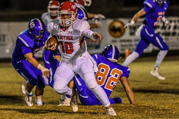 Heritage Academy quarterback Carter Putt scrambles for a first down during the first quarter.