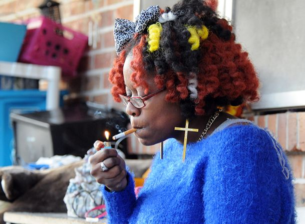 Shilica Rice, who lives at Connor Heights, lights a cigarette outside of her home Sunday. The federal government Thursday announced plans to ban smoking within 25 feet of any public housing.