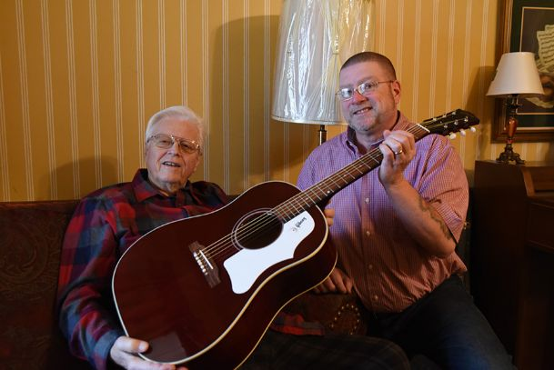Ministers Jerry Potter Sr. of Columbus, left, and his son Tim Potter of Valdosta, Georgia, hold a new Gibson J-45 acoustic guitar gifted to Tim in December. The instrument signifies more than a lifelong love of music the Potter family shares. It represents bonds grown even stronger during the elder Potter's kidney transplant surgery in November. Tim temporarily stood in for his father in the pulpit at Covenant Life Ministries in Columbus