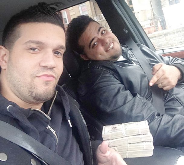 In this undated photo provided by the United States Attorney's Office for the Southern District of New York, Elvis Rafael Rodriguez, left, and Emir Yasser Yeje, pose with bundles of cash allegedly stolen using bogus magnetic swipe cards at cash machines throughout New York.