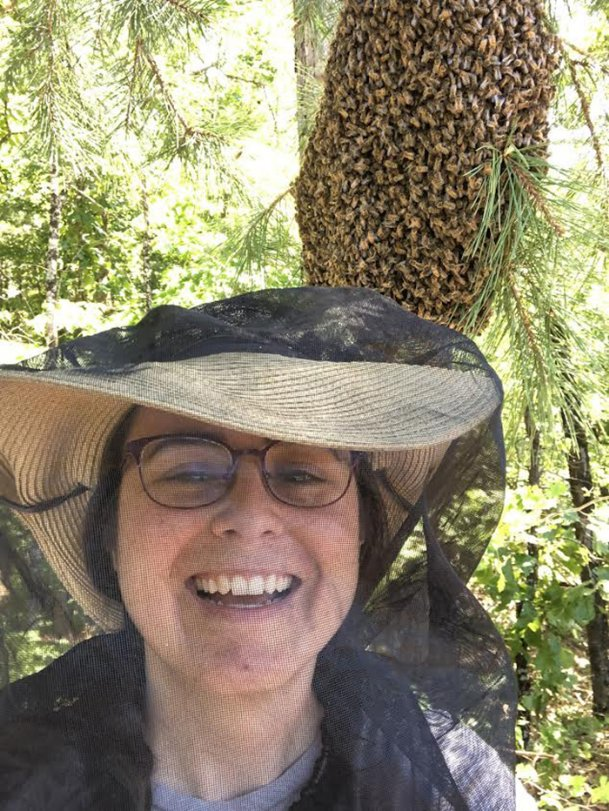 Beekeeper Ali Pinion of Starkville, with a net over her face, stands in front of a swarm of bees on a tree. Pinion has found her calling, carrying out bee removals and rescues.