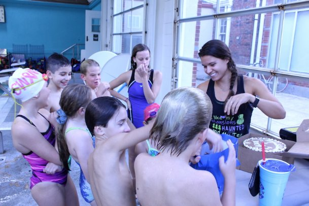 Swim Columbus swimmers crowd around coach Stephani Gonzalez, right, on Thursday at the downtown YMCA. Gonzalez was named age group swim coach of the year by her peers within Mississippi Swimming on Sunday, and her team honored her Thursday with a cake, a card and a blue bag full of candy.