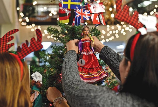Beth Gillian, left, puts a doll representing Ireland on the Columbus Air Force Base International Spouses Group tree in the Columbus-Lowndes Public Library Monday. At right, Olga Almazam adds a doll representing Mexico. The group researched multiple countries to make traditional dress for more than three dozen dolls for the tree, part of the library's annual Festival of Trees. Twenty-three trees decorated by local organizations and businesses will be on display throughout the month. The public is invited to an open house from 4-6 p.m. Thursday, Dec. 12 at the library at 314 Seventh St. N.