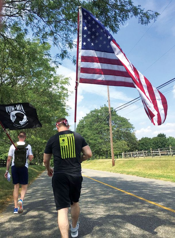 Maj. Jonathan Leetch, right, walks carrying the American flag while on a 100-mile march from New Jersey to Ground Zero in this 2018 photo. Leetch and Capt. Matthew Carpenter, both stationed at Columbus Air Force Base, made the trek again this year in a group of about 16 people who delivered the flag and a more than $10,000 donation to the National September 11 Memorial and Museum on Wednesday, the 18th anniversary of the attacks on the Twin Towers.