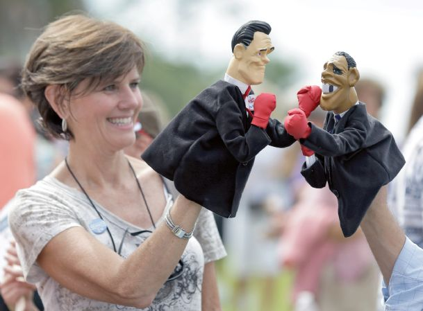 Lynn Armstrong Coffin and Eric Papalini, not shown, of PunchingPoliticians.com hold puppets of Republican presidential candidate and former Massachusetts governor Mitt Romney and President Obama boxing before a campaign rally at the Ringling Museum of Art Thursday in Sarasota, Fla.