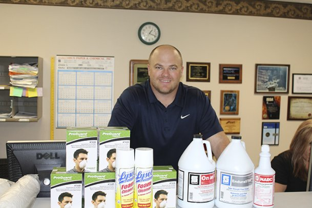 """E.J. Nolen stands behind a product display at Columbus Paper and Chemical on Military Road on Friday. The sales representative is also the third generation to be involved in the family business that started in 1967. Since the COVID-19 coronavirus outbreak came to the U.S., requests for hand sanitizer, disinfectant and toilet paper has skyrocketed for the janitorial supplies wholesaler, Nolen said. """"It's just nonstop,� he said."""