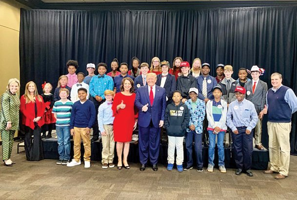 Liza Miley's language arts class at New Hope Middle School, along with some other New Hope students and staff, pose for a picture with President Donald Trump at Trump's rally at BancorSouth in Tupelo Friday. The students got to speak with Trump, as well as other politicians and journalists at the rally.