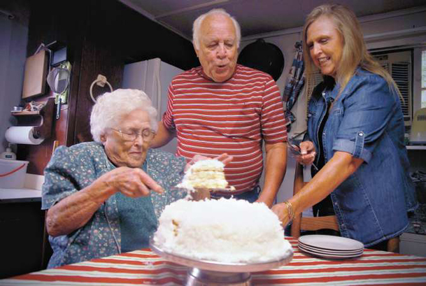 In her New Hope home, Lorene Thrasher serves coconut cake to her son, Buddy Thrasher, and daughter Angie Whitten. Thrasher will mark her 94th birthday Thursday.