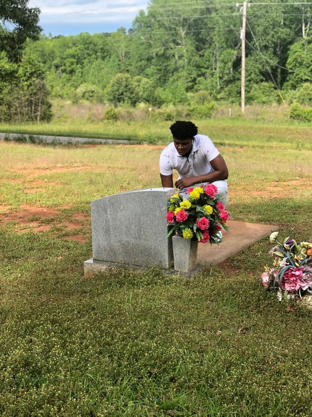 Tre'von kneels before his father's grave during a visit to Haven Chapel. He estimates he visits Ken's tombstone three to five times per year.