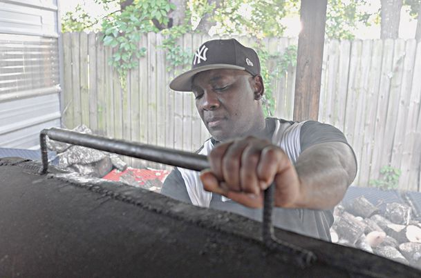Friday afternoon Ronnie Clayton of Brothers Keepers Barbecue tends one of two grills he uses to cook the ribs, rib tips, chicken, Boston butts and snouts he serves at his barbecue stand at the corner of Seventh Avenue North and 20th Street.