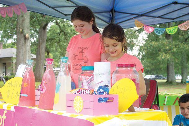 Kadie Eldridge, left, and Abigail McTaggart pour lemonade at their