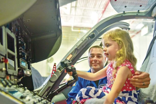 Jay Langford shows his daughter, River Langford, 3, the pilot's seat in AirCare 3, a helicopter that the University of Mississippi Medical Center is basing in Lowndes County. The helicopter was unveiled at Airbus on Thursday.
