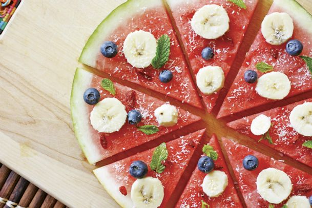 """Cheese and pepperoni have their place, but this cool, refreshing """"pizza� boasts chilled watermelon, banana slices, blueberries and coconut. Summer means fresh fruits are on center stage."""