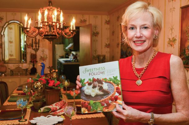 """Katy Smith Houston is pictured with her cookbook, """"Sweetness Follows: The Story of Sam and the Treat of the Week,� in the home of her longtime friend Dai Wilson of Columbus during a recent visit. The cookbook is a compilation (plus some) of dessert recipes Houston made every week for 62 weeks for a special young man recovering from traumatic brain injury. Houston is a alumna of Heritage Academy and Mississippi State, currently living in the Jackson area. She will attend a cookbook signing at Pizazz in Columbus Tuesday, March 12 from 11 a.m. to 2 p.m."""