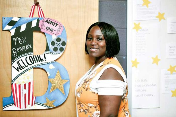 Stacee Bonner, first-year special education teacher, stands by her classroom door at Columbus Middle School Friday. Bonner worked as a custodian at Mississippi State University for seven years while taking classes to earn her master's and specialist degrees.
