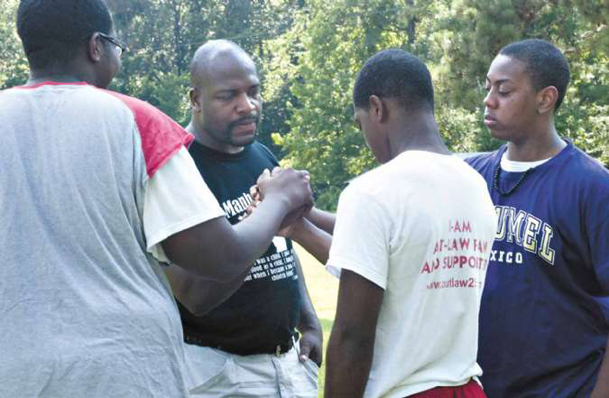 Edward Yeates, second from left and founder of Father's Child Ministry, clasps hands with Jared Jones, Juwan Roberts and William Nelson Saturday afternoon during the third annual Manhood Camp at Camp Pratt.