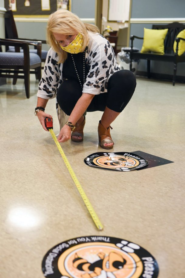 Principal Julie Fancher measures six feet between two decals to remind people about social distancing on Friday at Henderson Ward Stewart Elementary School in Starkville. Eight decals will be spread out in Henderson Ward Stewart Elementary's main office area to remind visitors to stay apart.