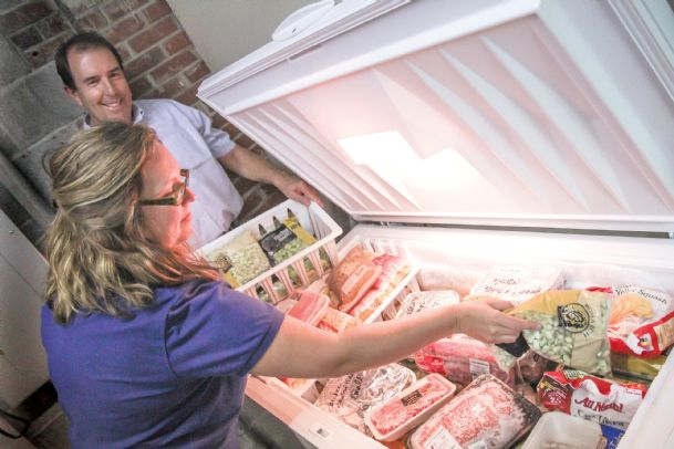 Martha Wooten of Community Counseling Services and community volunteer Wesley Platt load casseroles, meats and veggies into a freezer at the facility in downtown Columbus Monday. A new chest freezer filled with some of these foods and more is being raffled off by The Pines and Cady Hill Recovery Center as a fundraiser. Raffle tickets are $2.50 at the center at 1011 Main St., or at Financial Works, 401 Seventh St. N. The drawing will be during a block party Sept. 28.