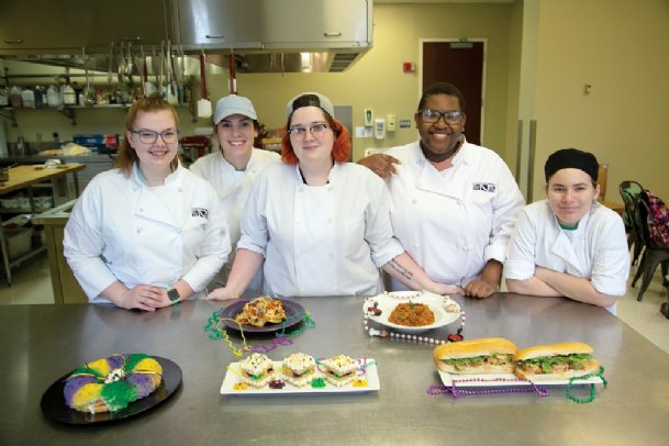 From left, Mississippi University for Women culinary arts students Lauren Weaver of Starkville, Sarah Grete of Clinton, Paige Lovette of Meridian, Alexa Hunt of Roxie and Ashton Rucker of Vaughan are pictured Feb. 11 with Mardi Gras dishes they made for their food styling course. Themed dishes prepared, from left in front, are king cake, opera cakes and fried shrimp po'boys with comeback sauce. Behind those are Cajun crayfish pasta, left, and Creole jambalaya.