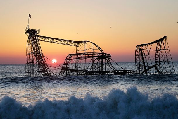 The sun rises in Seaside Heights, N.J., in a Feb. 25, 2013 file photo, behind the Jet Star Roller Coaster which has been sitting in the ocean after part of the Casino Pier was destroyed during Superstorm Sandy.