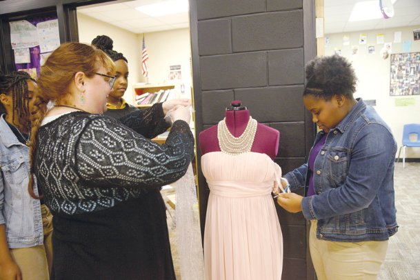 Chelsea Petty, Columbus Middle School drama instructor, helps her students Samara Bowman, Lexy Magee and Laylah Berry design a dress for an upcoming spring musical,
