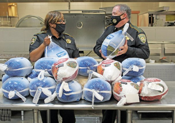 One way to make Thanksgiving memories is to do for others. On Thursday, Rhonda Sanders of the Community Benefit Committee, left, and Lowndes County Sheriff Eddie Hawkins show off frozen turkeys donated for a local turkey drive, a partnership of the Benefit Committee, the Sheriff's Department and the City of Columbus. Due to pandemic concerns, instead of cooking and giving out prepared meals this year as usual, volunteers distributed hundreds of the whole turkeys Saturday at the Columbus Soccer Complex.
